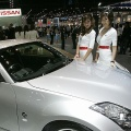 Thai models pose next to a Nissan 350Z from Japan on display at Thailand