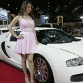Thai models pose next to a Bugatti Veyron from Italy on display at Thailand International Motor Expo