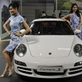Models pose next to a Porsche 911 sportscar at the Beijing Auto Show