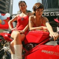 Models pose next to a Ducati motocycle during the Classic Auto-Cycle Museum