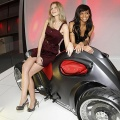 Models pose with 4-wheel motorcycle 'Sfarro Pendolauto' during a press presentation prior