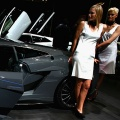 Models stand next to a Lamborghini Gallardo Supperleggera at the 77th International Motor Show
