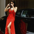 A model takes a picture of a Ferrari at the 77th International Motor Show