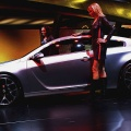 Models stand next to the Opel GTC cocept at the 77th International Motor Show