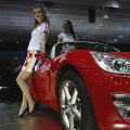 Models stand next to a Opel GT at the 77th International Motor Show