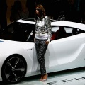 A model stands next to a FT-HS Hybrid Sports from Toyota at the 77th International Motor Show