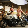 Models pose on a BMW K1200R motorcycle during the International Motorcycle and Scooter