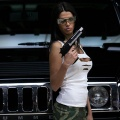 A model poses in front of a Hummer, the jeep based on a US military vehicle that has become a status symbol