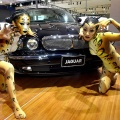 South Korean models pose by a Jaguar new XJ Super V8 during the Seoul Motor Show in Ilsan