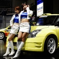 Models smile beside Suzuki Swift super 1600 concept during the Tokyo Auto Salon