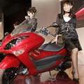 Models pose next to Japanese motorcycle giant Yamaha Motor's new large scooter 'Majesty'