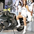 Promotion girls show off Taiwanese motorcycle maker PGO's 'PMX sports' scooter during the 33th Tokyo Motorcycle Show
